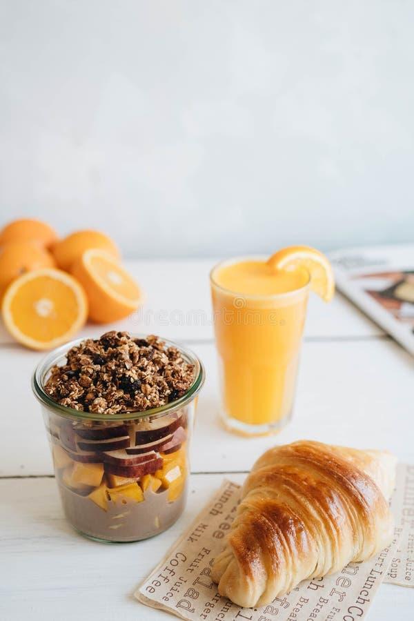 在桌上的可口早餐 新鲜的橙汁过去、水果沙拉和新月形面包在白色桌上 库存图片