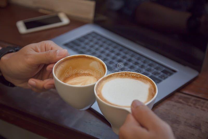 在桌上的咖啡拿铁艺术和膝上型计算机与遇见友谊的人与技术概念一起 免版税库存图片