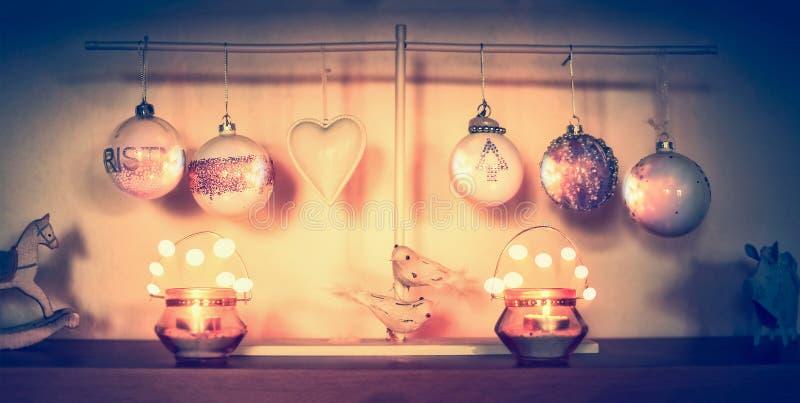在桌上的圣诞节家庭装饰与球、蜡烛和bokeh 库存图片