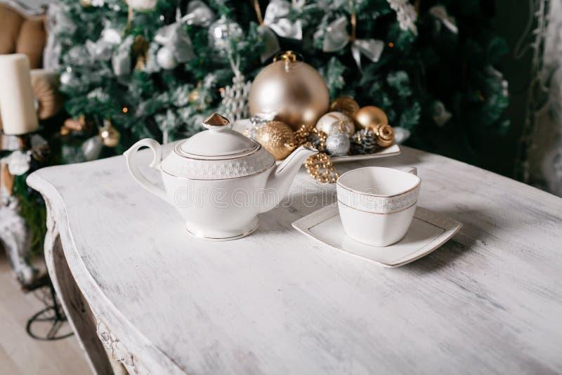 在桌上的圣诞节装饰以用分支和诗歌选云杉装饰的壁炉为背景 免版税库存照片