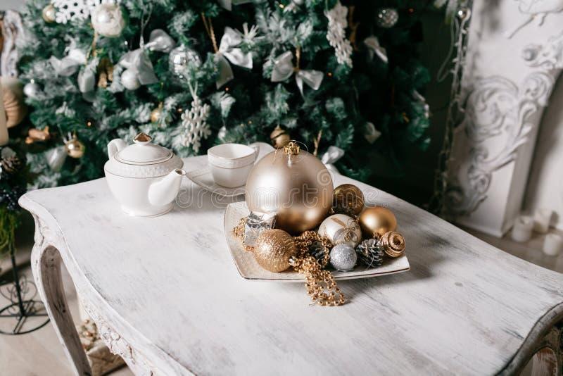 在桌上的圣诞节装饰以用分支和诗歌选云杉装饰的壁炉为背景 免版税图库摄影
