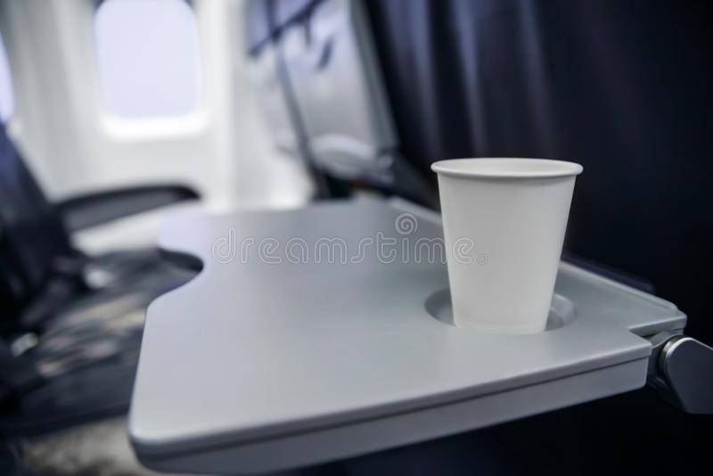 在桌上的塑料杯子在飞行期间的飞机 酒精消耗量在船上 免版税图库摄影
