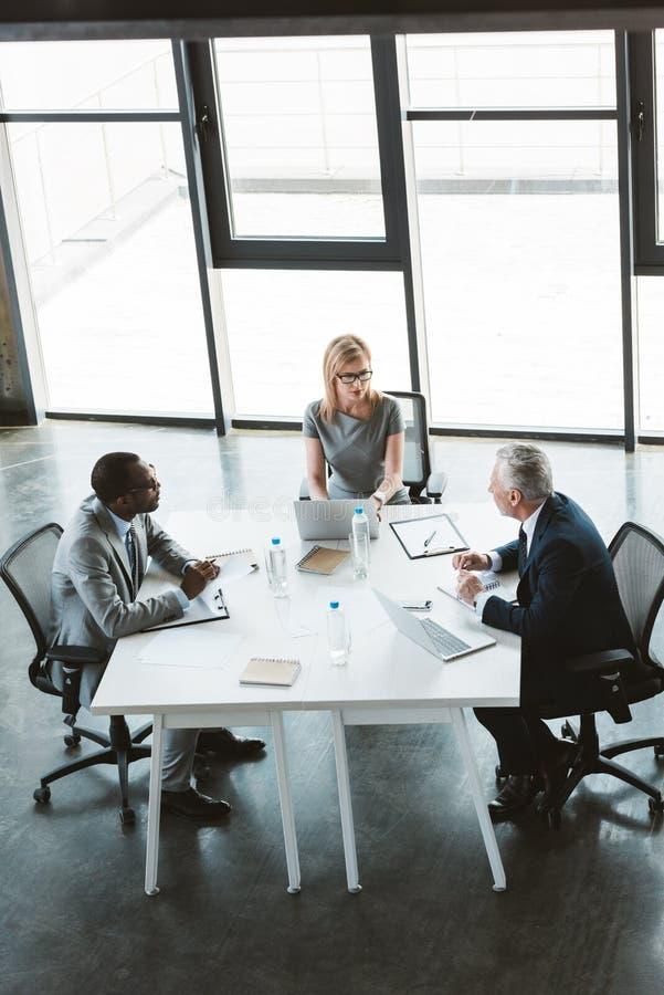 在桌上的大角度观点的专业不同种族的商人 免版税库存照片