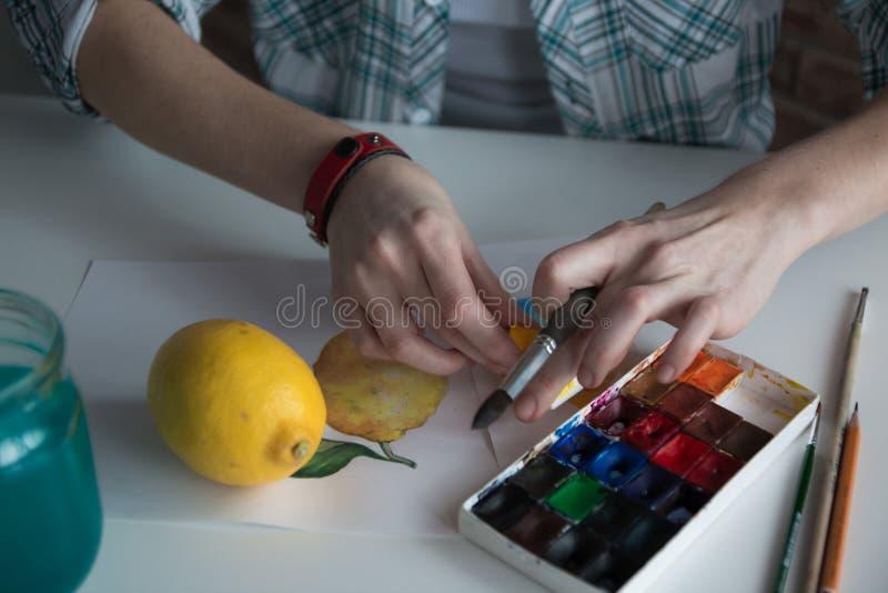 在桌上的女性艺术家` s手 免版税库存图片