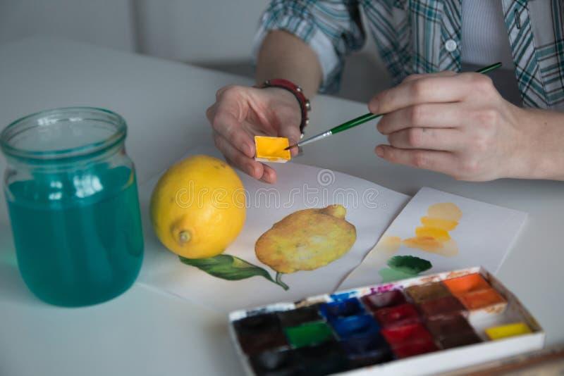 在桌上的女性艺术家` s手 免版税库存照片