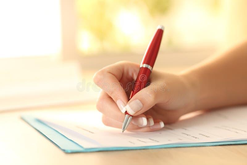 在桌上的妇女手填装的形式 免版税图库摄影