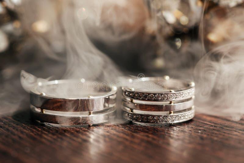 在桌上的婚姻的白色圆环与烟 免版税库存图片