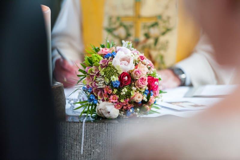在桌上的婚姻的花束在新娘和新郎之间 图库摄影