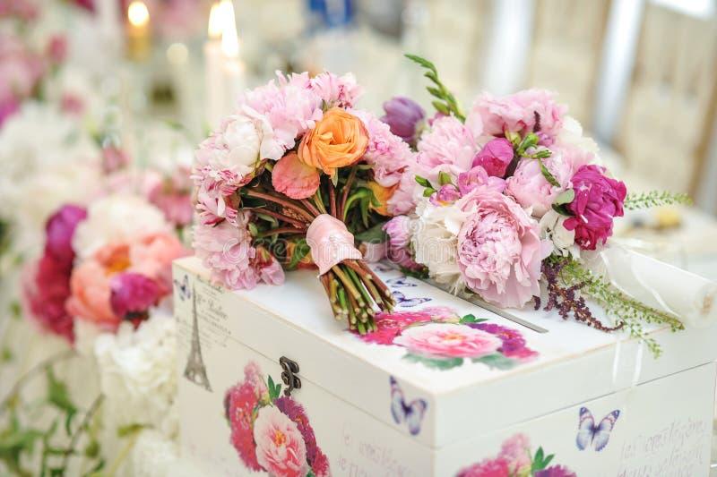 在桌上的婚礼装饰 植物布置和装饰 桃红色和白花的安排在事件的餐馆 免版税库存图片