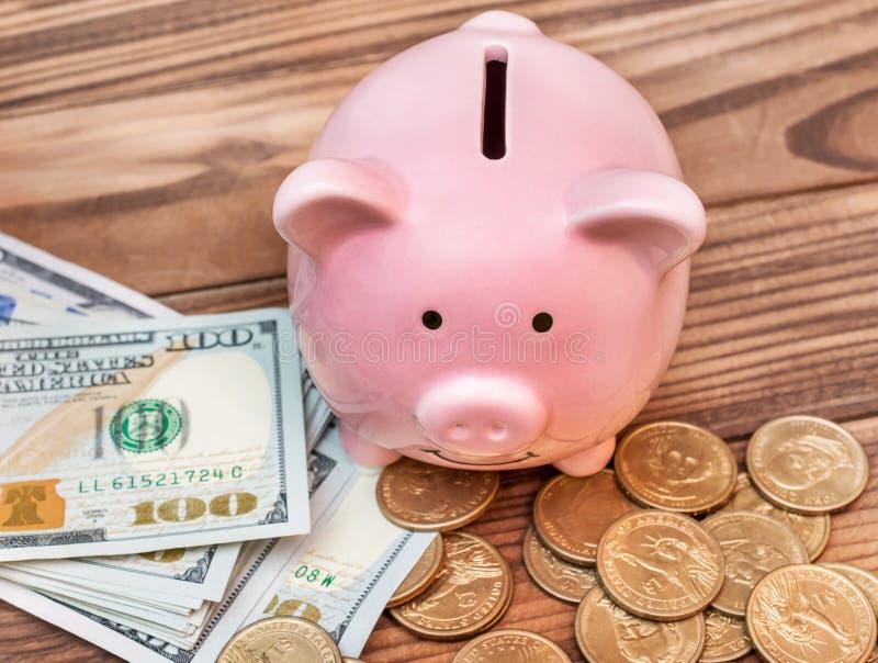 在桌上的存钱罐与美金和硬币 库存图片