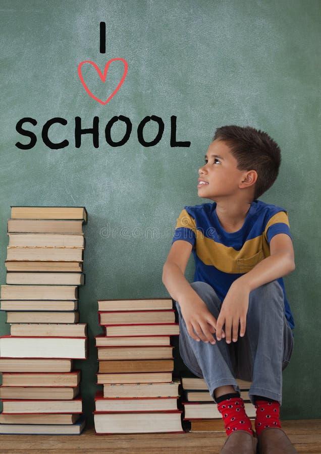 在桌上的学生男孩认为反对与I爱学校课文的绿色背景的 免版税库存照片