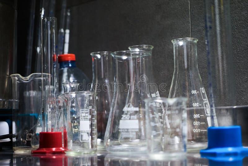 在桌上的实验室玻璃器皿反对灰色背景,特写镜头 图库摄影