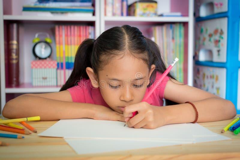 在桌上的小女孩图画在家 免版税库存图片