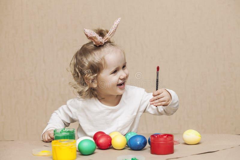 在桌上的小逗人喜爱的婴孩颜色复活节彩蛋在颜色,愉快 库存图片