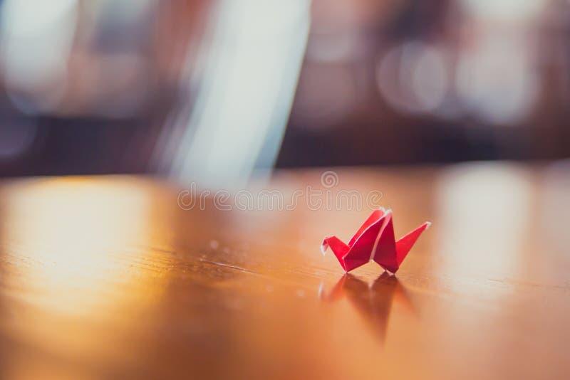 在桌上的微小的红色origami起重机 免版税图库摄影