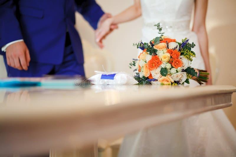 在桌上的新娘花束在结婚登记期间仪式  复制空间 免版税库存照片