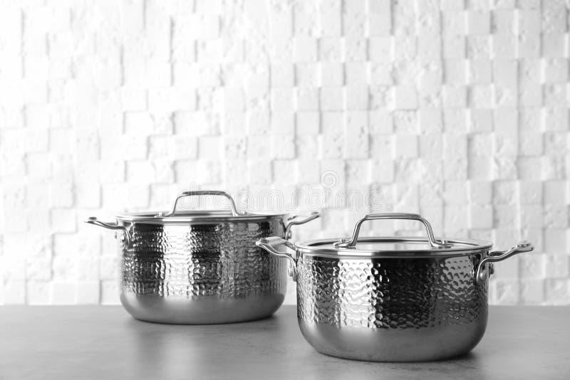 在桌上的新的干净的平底深锅对白色墙壁 免版税图库摄影