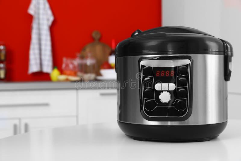 在桌上的新的现代多烹饪器材在厨房里 库存图片