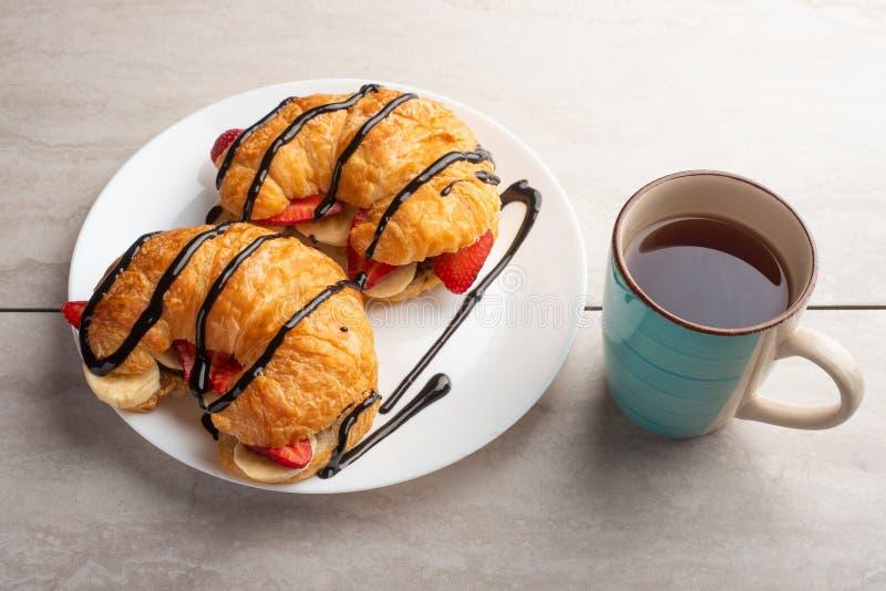在桌上的新鲜的新月形面包,用热的茶、草莓和香蕉,可口早餐 免版税库存图片