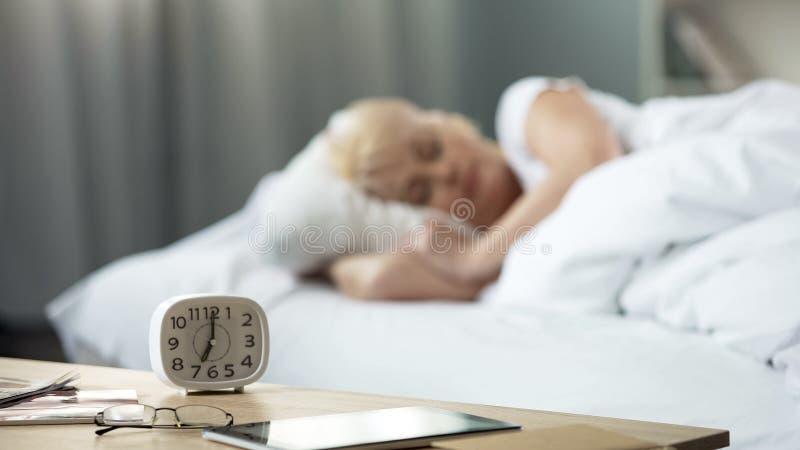 在桌上的时钟与睡觉在背景,早晨的床上的中年女性 免版税库存照片