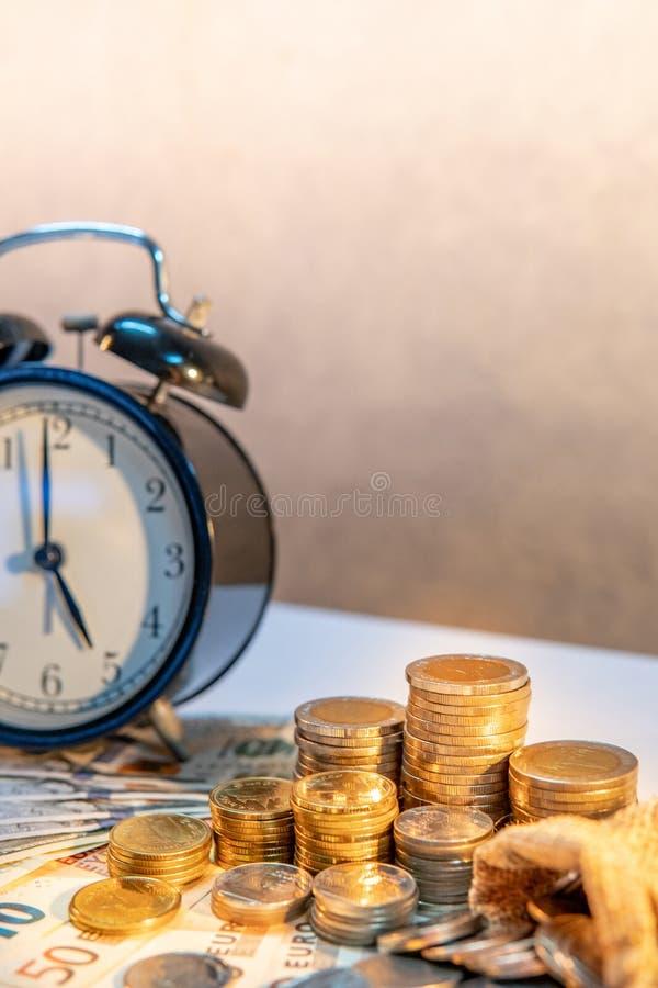 在桌上的时钟和硬币堆 时间投资 库存照片