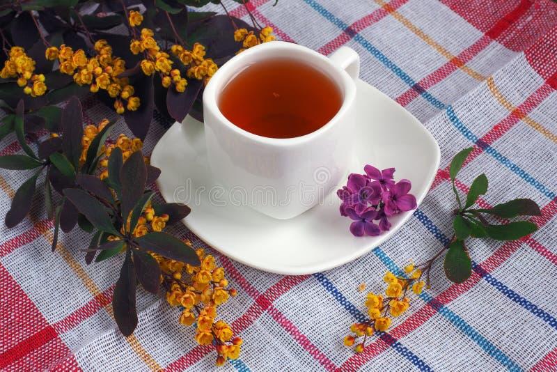 在桌上的春天茶与丁香花束  免版税库存照片