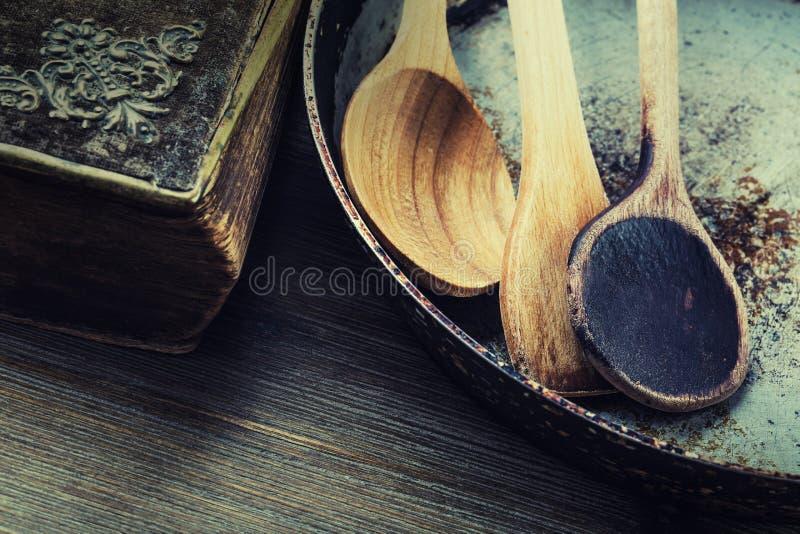 在桌上的木厨房器物 在一个减速火箭的样式的食谱书木匙子在木桌上 库存照片