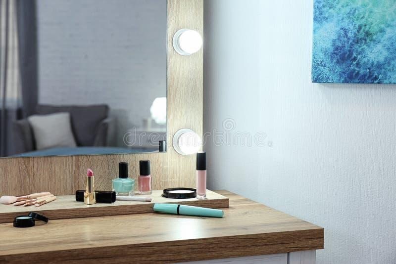 在桌上的构成镜子在白色墙壁附近 库存图片