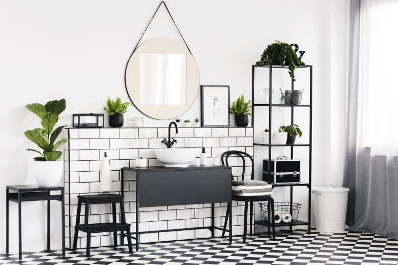 在桌上的植物在与方格的地板和镜子的黑白卫生间内部 实际照片 免版税库存图片