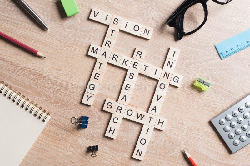 在桌上的概念性企业主题词与做纵横填字谜的比赛的元素 免版税库存照片