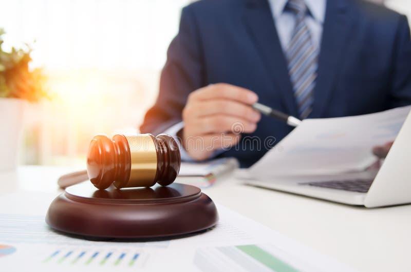 在桌上的正义标志木惊堂木 工作在办公室的律师 免版税图库摄影