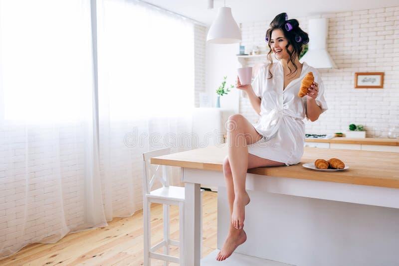 在桌上的正面快乐的年轻女人在厨房里 无忧无虑的管家藏品杯子和新月形面包在手上 ?? ?? 免版税库存图片