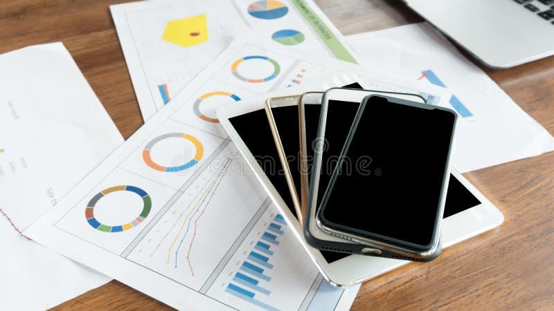 在桌上的流动聪明的电话堆有业务报告背景 免版税库存照片