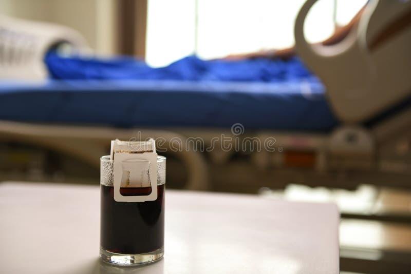 在桌上的滴水咖啡与床背景的患者 库存图片