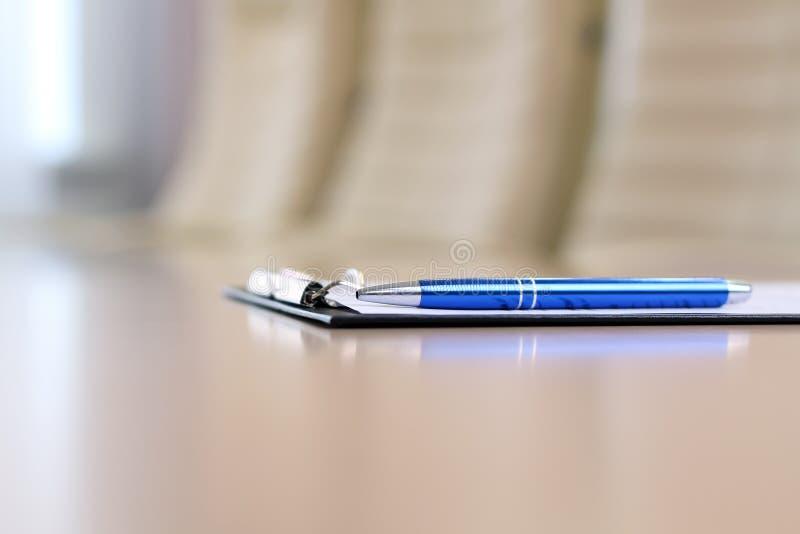 在桌上的特写镜头笔在业务会议前的空的公司会议室 免版税库存照片