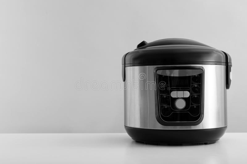 在桌上的现代电多烹饪器材反对灰色背景 图库摄影
