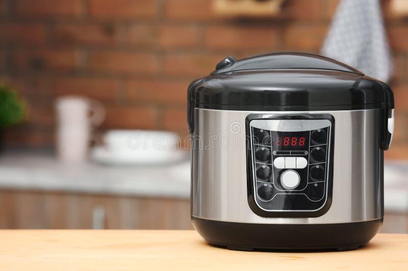 在桌上的现代电多烹饪器材在厨房里 免版税库存照片