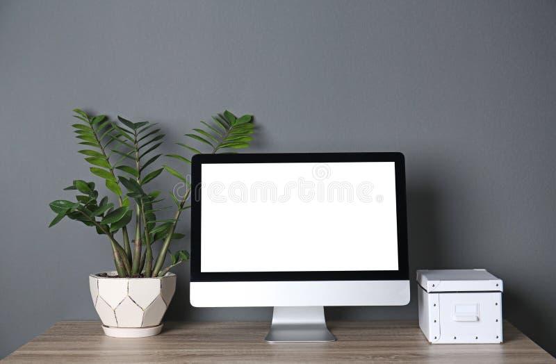 在桌上的现代计算机显示器对墙壁 嘲笑与文本的空间 免版税图库摄影