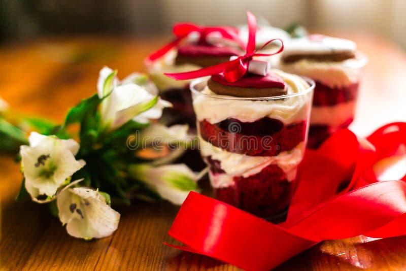 在桌上的琐事蛋糕与红色丝带和花 库存照片