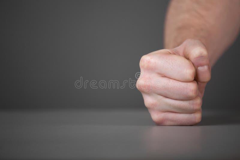在桌上的男性拳头。 库存图片
