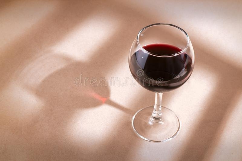 在桌上的红葡萄酒玻璃与窗口阴影 库存照片
