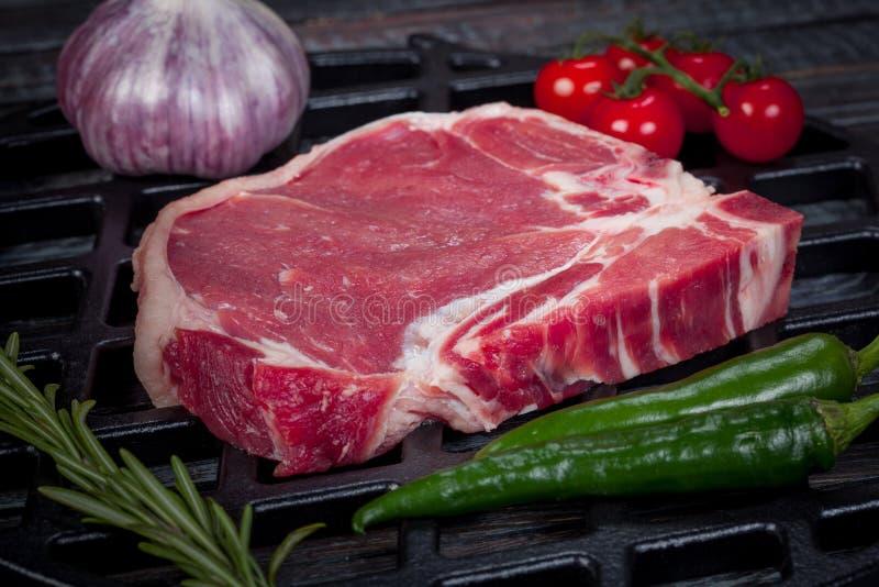 在桌上的美丽和水多的未加工的牛排与准备好的成份烤 免版税库存图片