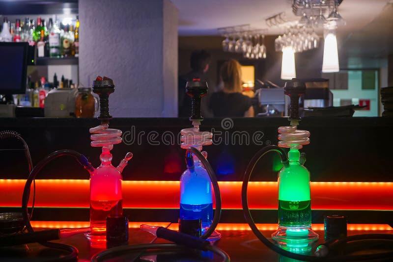 在桌上的美丽的玻璃水烟筒在酒吧 免版税库存图片