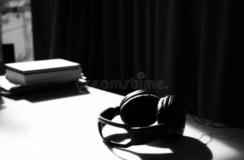 在桌上的耳机与阳光感受放松 图库摄影