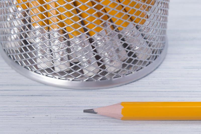 在桌上的背景,在铅笔点的杯座和橡皮擦特写镜头 图库摄影