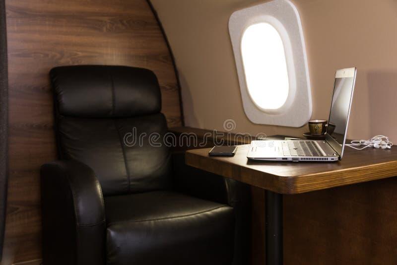 在桌上的膝上型计算机在一个私人喷气式飞机内部 E 免版税库存照片
