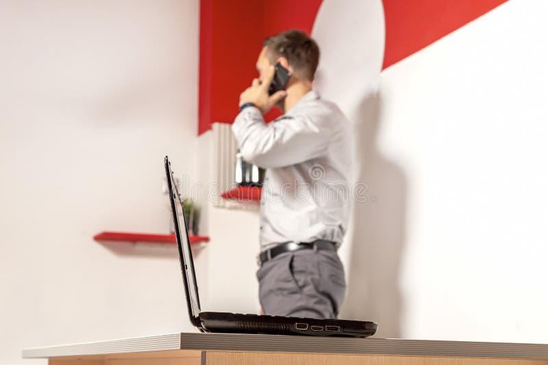 在桌上的膝上型计算机在办公室 反对在迷离的背景,一个年轻商人在电话谈话并且看起来不错 库存照片