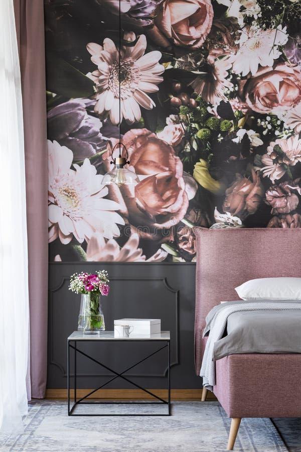 在桌上的花在卧室内部的桃红色床旁边与被仿造的墙纸 实际照片 图库摄影