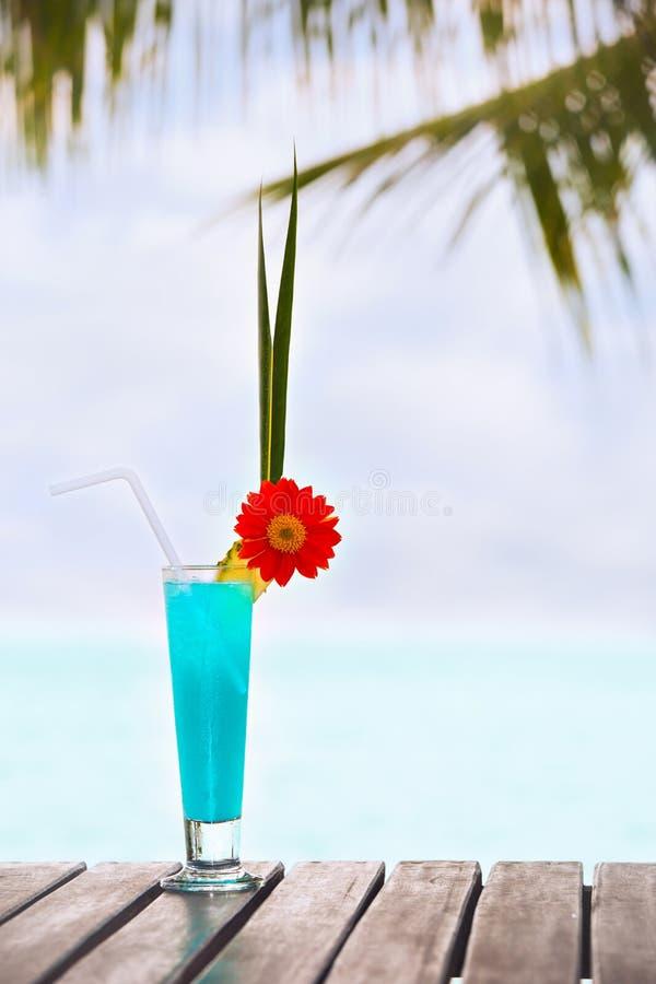在桌上的蓝色盐水湖鸡尾酒在热带海滩 免版税图库摄影