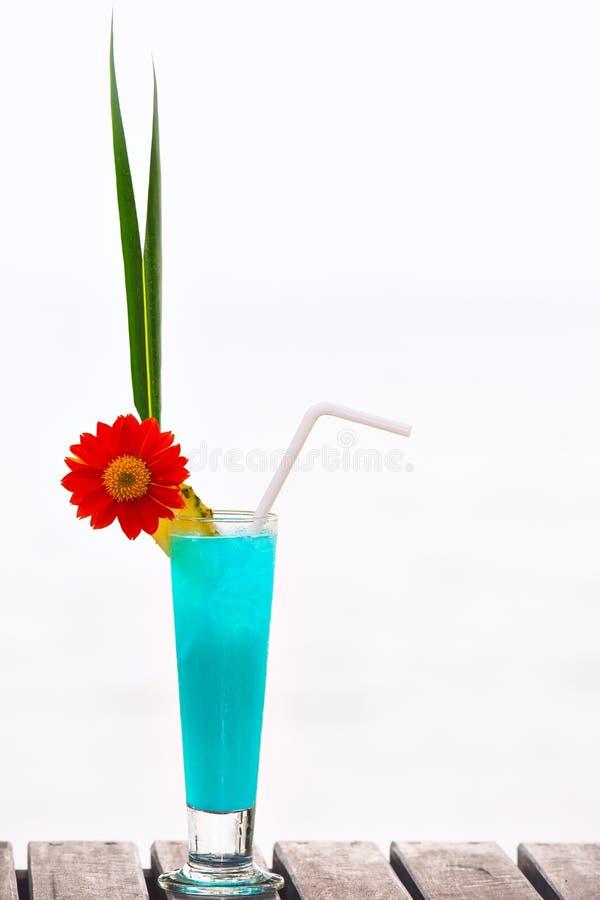 在桌上的蓝色盐水湖鸡尾酒在热带海滩 免版税库存照片
